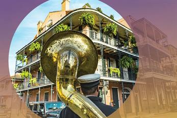 Tuba player facing a building located in New Orleans, in representation of the Health Academy Conference taking place in New Orleans
