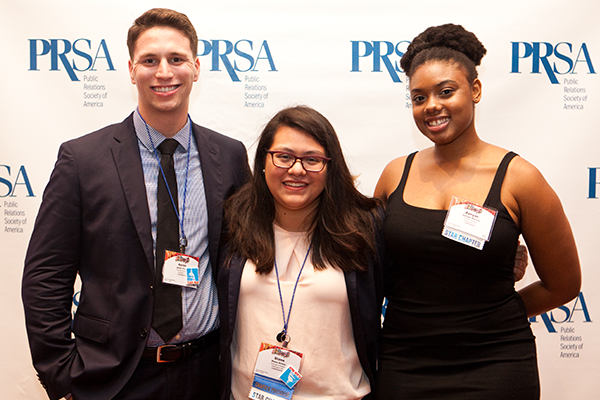 Three PRSA members smiling at the camera standing infront of a PRSA step-and-repeat. They are dressed in business and formal attire.