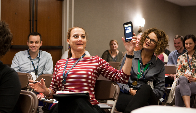 A PRSA member holding up her phone in a learning session at a conference as part of a demonstration.