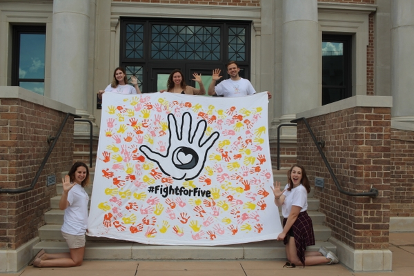Louisiana State University Bateman Participants holding a tarp that reads 3fight for five