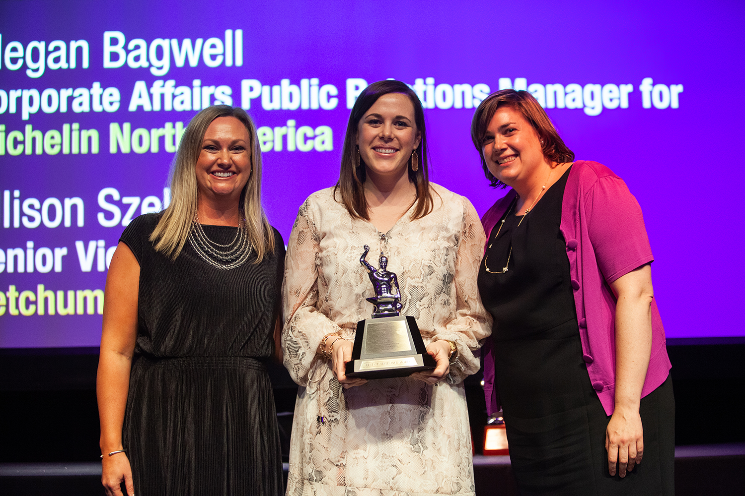 Michelin standing in-between two people, holding her Silver Anvil trophy at the International Conference