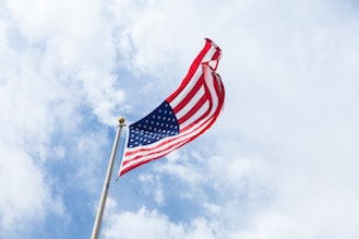 American flag waving in the wind with clouds and blue sky behind it